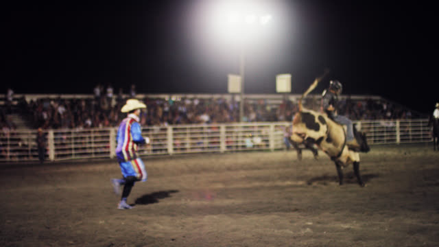 Slow Motion Shot of a Bull Rider Competing in a Bull Riding Event before Being Thrown from the Bull's Back while the Rodeo Clown Distracts the Bull in a Stadium Full of People at Night