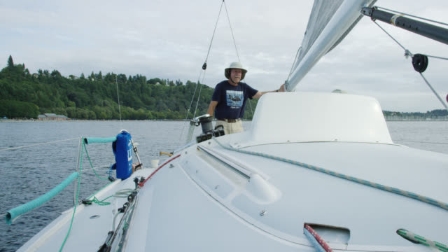 Slow Motion Shot of a Captain Checking the Mainsail while His Small Crew Works on the Deck of a Sailboat in Puget Sound near Seattle, Washington
