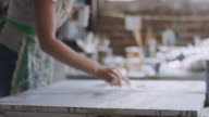 istock Slow Motion Shot of a Caucasian Female Artist Painting with a Paint Knife on a Canvas in Her Indoor Art Studio 1217897586