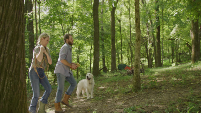 Slow Motion Shot of a Caucasian Man and Woman in Their Forties Climbing a Hill with Their Dog in a Lush Forest before Reaching a Horse Barn on a Sunny Day in Tennessee