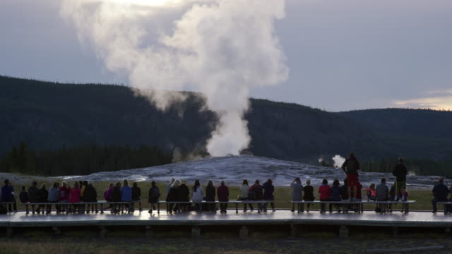 Slow Motion Shot of a Crowd of People Waiting for Old Faithful Geyser to Erupt as It Steams in Yellowstone National Park on an Overcast Day