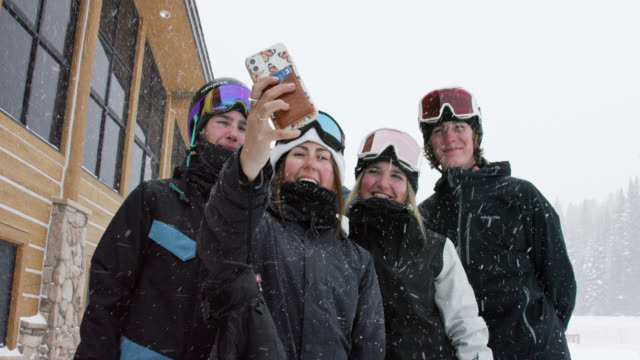 Slow Motion Shot of a Group of Young Snowboarders and Skiers (Men and Women) in Their Twenties Taking a Selfie on a Cell Phone at Eldora Ski Resort near Boulder, Colorado on a Snowy, Overcast Day