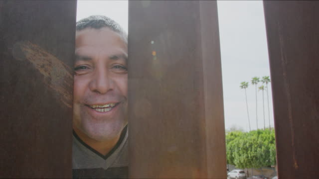 slow motion shot of a hispanic man in his forties peeking through the steel-slat border wall between mexico and the united states while smiling and laughing at the camera filming him from the us side - ogrodzenie granica filmów i materiałów b-roll