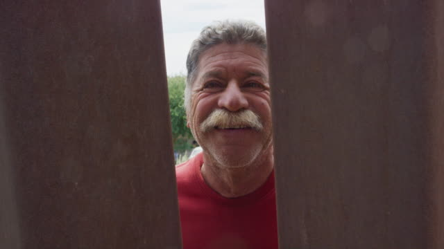 Slow Motion Shot of a Hispanic Man in His Sixties with a Mustache (on the Mexican Side) Peeking through the Steel-Slat Border Wall between Mexico and the United States with Several Other Hispanic, Male Friends while Smiling at the Camera Filming from the