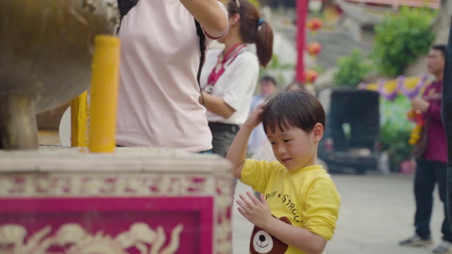 Slow motion shot of a Little boy travel with family and pray at dragon temple kammalawat in chinese new year