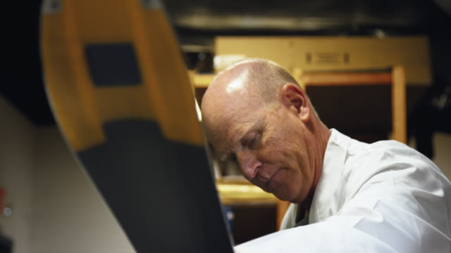 slow motion shot of a male caucasian ski technician in his fifties inspecting and repairing a downhill ski in an indoor repair shop - negozio sci video stock e b–roll