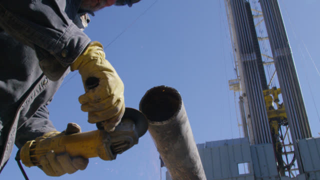 Slow Motion Shot of a Male Oilfield Worker in His Sixties Grinding and Filing a Metal Pipe Next to a Derrick at an Oil and Gas Drilling Pad Site on a Sunny Morning