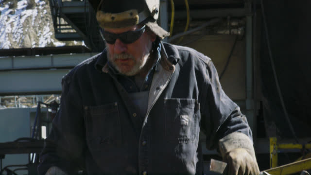 Slow Motion Shot of a Male Oilfield Worker in His Sixties Wearing a Welding Mask Carries a Hammer and a File Next to a Derrick at an Oil and Gas Drilling Pad Site on a Sunny Day