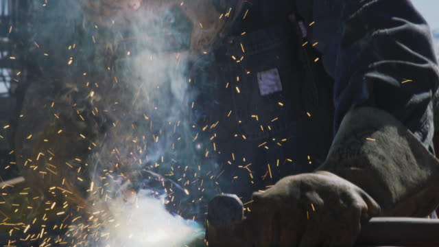 Slow Motion Shot of a Male Oilfield Worker in His Sixties Welding Two Pipes Together as Sparks Fly Next to a Derrick before He Pulls Up His Welding Mask and Inspects His Work at an Oil and Gas Drilling Pad Site on a Sunny Day