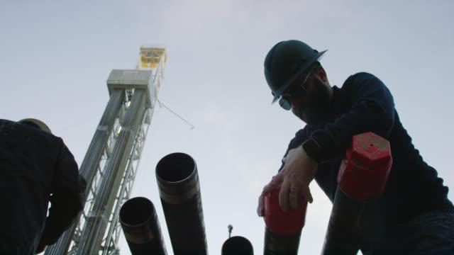 slow motion shot av en manlig oljefält worker sätta på en drilling pipe thread protector cap med en derrick bakom honom på en olja och gas drilling pad site - pipeline bildbanksvideor och videomaterial från bakom kulisserna