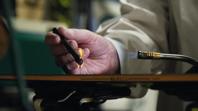 slow motion shot of a male ski technician using a blow torch to melt and drip a ptex candle on to the base of a ski to repair a gouge in an indoor repair shop - negozio sci video stock e b–roll