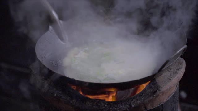 vídeos y material grabado en eventos de stock de tiro de cámara lenta de un hombre cocinando con carbón de leña de la estufa. plato de tallarines en el wok sobre fuego abierto. comida callejera en el barrio chino de bangkok, tailandia - comida china