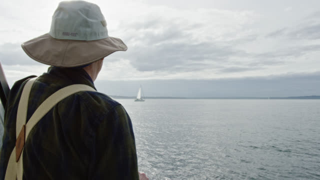 Slow Motion Shot of a Man in His Sixties Looking out over Puget Sound in Washington from the Deck of a Sailboat on a Partly Cloudy Day Slow Motion Shot of a Man in His Sixties Looking out over Puget Sound in Washington from the Deck of a Sailboat on a Partly Cloudy Day mast sailing stock videos & royalty-free footage