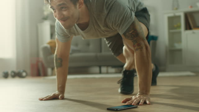 vídeos de stock e filmes b-roll de slow motion shot of a muscular fit man in t-shirt and shorts is doing mountain climbers while using a stopwatch on his phone. he is training at home in his spacious and bright living room with minimalistic interior. - home