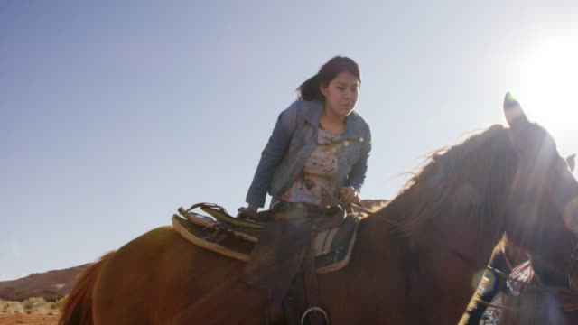 Slow Motion Shot of a Native American (Navajo) Girl in Her Teens Mounting Her Horse while Another Woman Calms the Horse on a Bright, Sunny Day in the Desert of Arizona