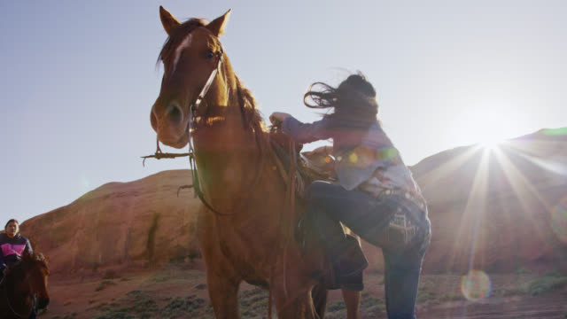 Slow Motion Shot of a Native American Girl (Navajo) in Her Teens Mounting Her Horse while Another Teenaged Girl Watches in the Monument Valley Desert in Arizona/Utah on a Sunny Day Next to a Large Rock Formation