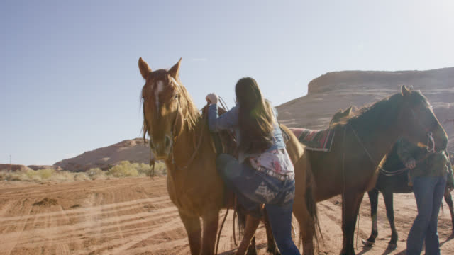 Slow Motion Shot of a Native American (Navajo) Girl in Her Teens Stepping up on to a Stirrup before Mounting Her Horse on a Bright, Sunny Day in the Desert of Arizona
