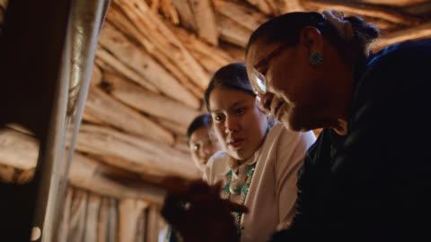slow motion shot native american babcia (navajo) w jej sześćdziesiątych nauczania jej nastoletnich wnuczek jak splot w loom indoors w hogan (navajo hut) - kultury filmów i materiałów b-roll