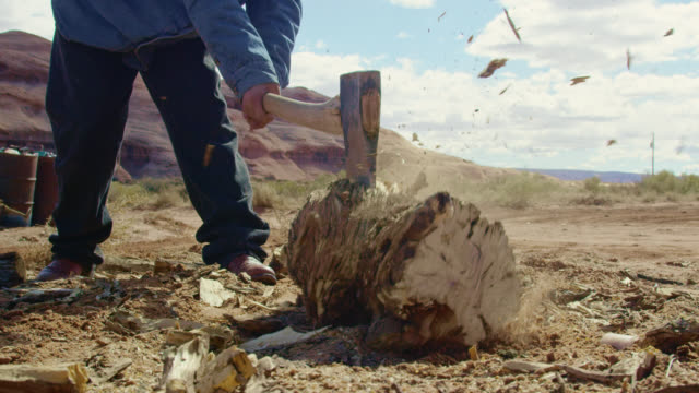 Slow Motion Shot of a Native American Teenaged Boy Using an Axe to Chop Firewood in Monument Valley in Arizona/Utah on a Clear, Sunny Day with a Large Rock Formation Behind Him Slow Motion Shot of a Native American Teenaged Boy Using an Axe to Chop Firewood in Monument Valley in Arizona/Utah on a Clear, Sunny Day with a Large Rock Formation Behind Him firewood stock videos & royalty-free footage