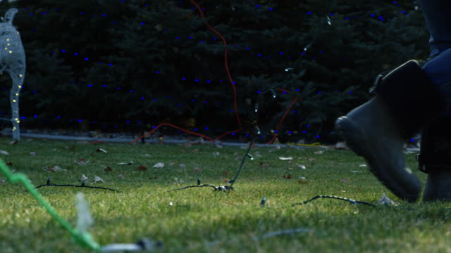 Slow Motion Shot of a Person Walking and Pulling a String of Lights While Decorating for Christmas Outdoors