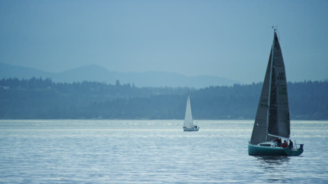 Slow Motion Shot of a Sailboat with a Small Crew Heading Out into the Puget Sound in Washington on an Overcast Day