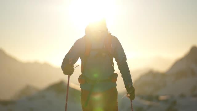 slow motion shot of a skier crossing a snow field with sun behind - spektakularny krajobraz filmów i materiałów b-roll