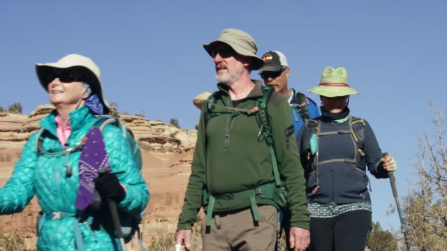 slow motion shot of a small group of mature caucasian men and women hiking together in the rocky high desert mountains of western colorado on a clear, sunny day - riserva naturale parco nazionale video stock e b–roll