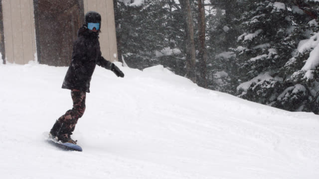 Slow Motion Shot of a Snowboarder in Full Winter Gear Exiting a Ranger Station and Snowboarding Down a Run at Eldora Ski Resort near Boulder, Colorado on a Snowy, Overcast Day