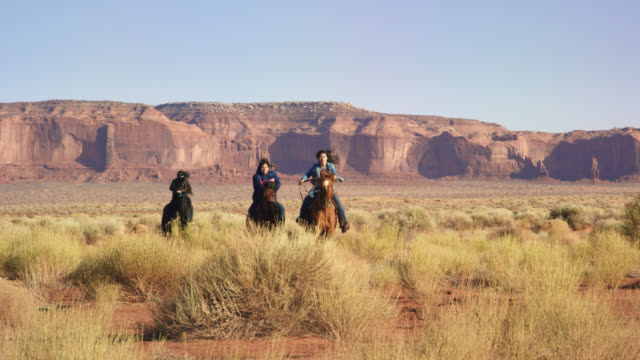 Slow Motion Shot of a Teenaged Native American Children (Navajo) Galloping on Their Horses through the Monument Valley Desert in Arizona/Utah on a Sunny Afternoon