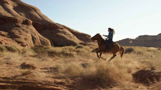 Slow Motion Shot of a Teenaged Native American Girl (Navajo) Galloping on Her Horse through the Monument Valley Desert in Arizona/Utah on a Sunny Afternoon Slow Motion Shot of a Teenaged Native American Girl (Navajo) Galloping on Her Horse through the Monument Valley Desert in Arizona/Utah on a Sunny Afternoon rock formations stock videos & royalty-free footage