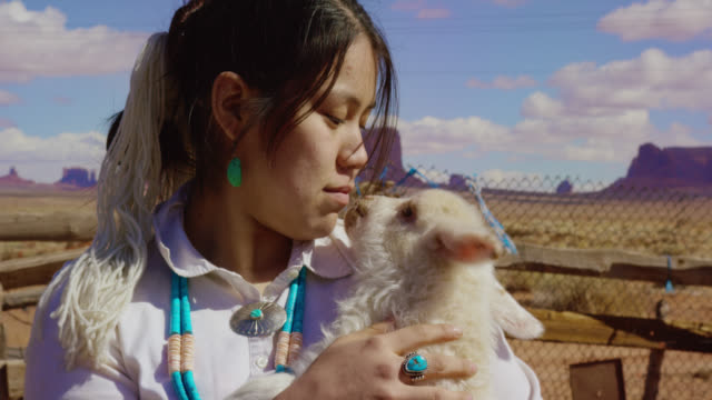 Slow Motion Shot of a Teenaged Native American Girl Holding a Lamb Close to Her Face in Monument Valley, Arizona/Utah on a Sunny Day with Large Rock Formations in the Background
