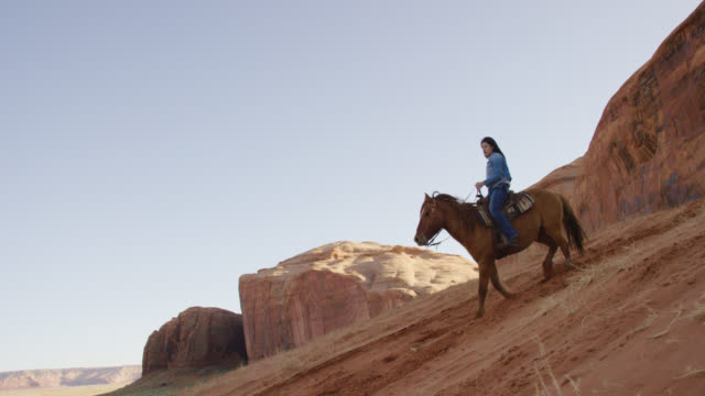 Slow Motion Shot of a Teenaged Native American Girl (Navajo) Riding Her Horse Down a Steep Hill with Her Dog in the Monument Valley Desert in Arizona/Utah at Sunset Next to a Large Rock Formation Slow Motion Shot of a Teenaged Native American Girl (Navajo) Riding Her Horse Down a Steep Hill with Her Dog in the Monument Valley Desert in Arizona/Utah at Sunset Next to a Large Rock Formation minority groups stock videos & royalty-free footage