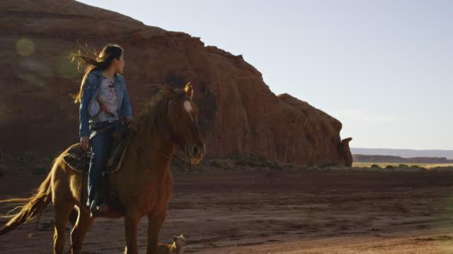 Slow Motion Shot of a Teenaged Native American Girl (Navajo) Sitting on Her Horse and Looking over the Landscape of the Monument Valley Desert in Arizona/Utah at Sunset Next to a Large Rock Formation Slow Motion Shot of a Teenaged Native American Girl (Navajo) Sitting on Her Horse and Looking over the Landscape of the Monument Valley Desert in Arizona/Utah at Sunset Next to a Large Rock Formation minority groups stock videos & royalty-free footage
