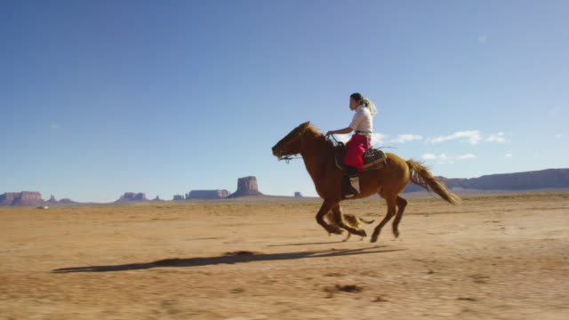 Slow Motion Shot of a Teenaged Native American Girl Wearing Traditional Navajo Clothing Galloping on Her Horse across the Monument Valley Desert with Her Pet Dogs with Large Rock Formations in the Distance on a Clear, Bright Day
