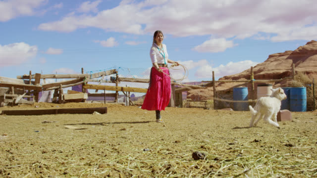 Slow Motion Shot of a Teenaged Native American Girl Wearing Traditional Navajo Clothing Roping/Lassoing a Lamb in a Fenced In Pasture as Sheep Run Past in Monument Valley, Arizona/Utah on a Sunny Day with a Large Rock Formation in the Background