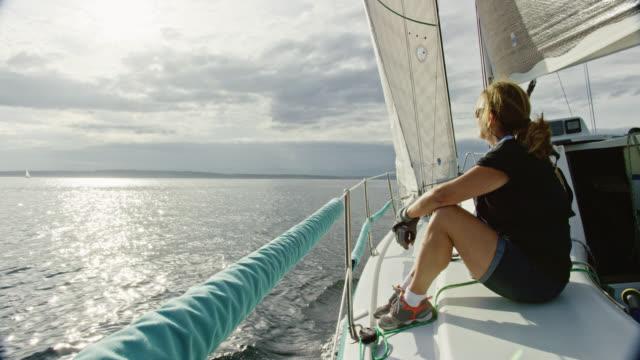 scatto al rallentatore di una donna sulla sessera anni seduta e guardando puget sound a washington dal ponte di una barca a vela in una giornata parzialmente nuvolosa - andare in barca a vela video stock e b–roll