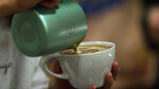 slow motion shot von einer frau hände gießen gedämpfte milch in einen becher voller espresso (kaffee), machen latte kunst in einem coffee shop - cappuccino stock-videos und b-roll-filmmaterial