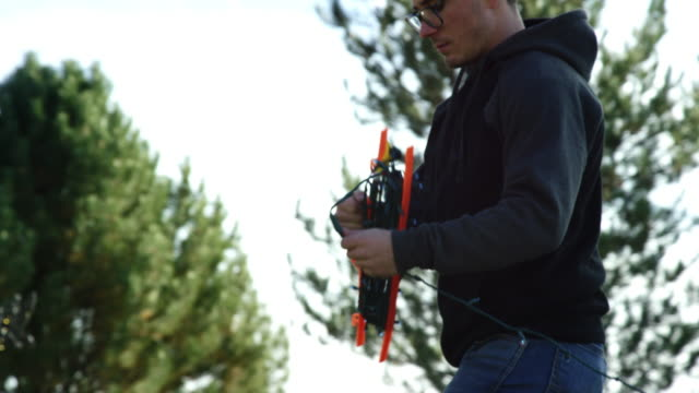 slow motion shot of a young caucasian man in his twenties unstringing christmas lights while decorating for christmas outdoors - decorare video stock e b–roll