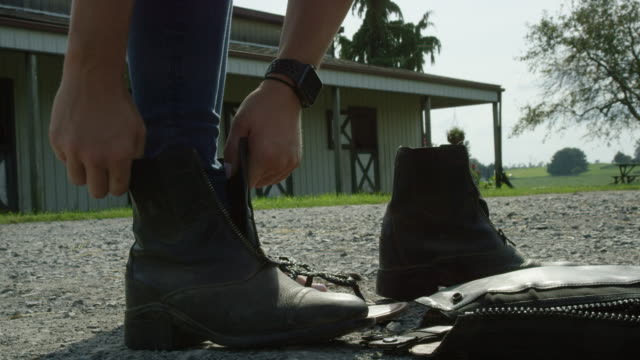 Slow Motion Shot of a Young Woman in Jeans Putting on Black Horse Riding Boots with a Stable in the Background on a Sunny Day at a Horse Farm