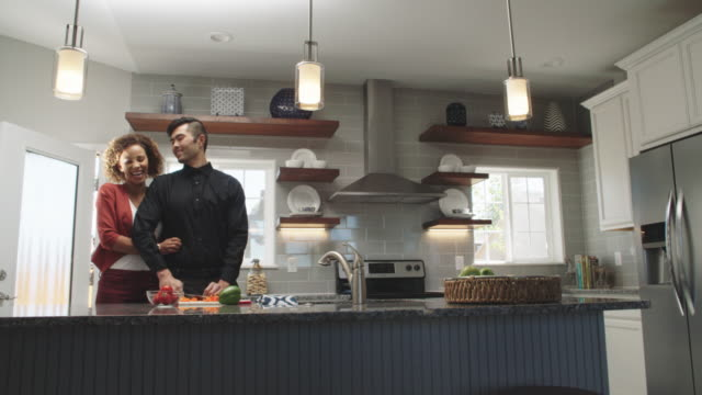 Slow Motion Shot of a Young Woman of Mixed Race Walking into the Room and Hugging a Young Asian Man from Behind as He Slices Vegetables with a Kitchen Knife on the Counter of a Bright, Modern Kitchen Slow Motion Shot of a Young Woman of Mixed Race Walking into the Room and Hugging a Young Asian Man from Behind as He Slices Vegetables with a Kitchen Knife on the Counter of a Bright, Modern Kitchen falling in love stock videos & royalty-free footage