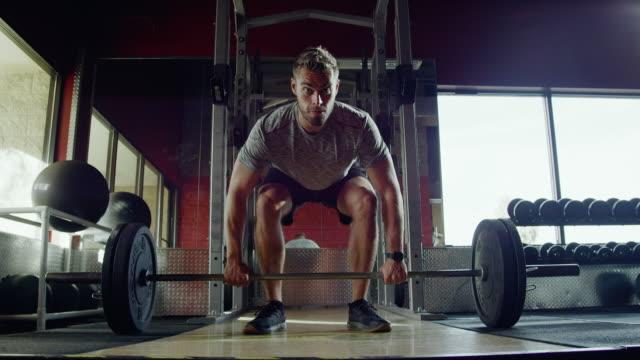 slow motion shot eines attraktiven kaukasischen mannes in seinen zwanzigern performing deadlifts mit einer langhantel beim gewichtheben in einem fitnessstudio - gewichtheben stock-videos und b-roll-filmmaterial