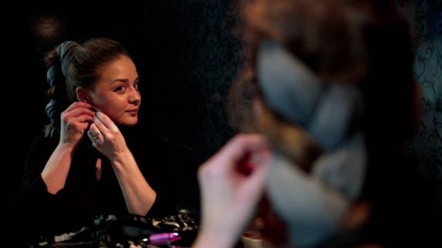 yavaş çekim çekici bir genç kadın küpe üzerinde koyarak bir tarih için hazırlanıyor - çekici insanlar stok videoları ve detay görüntü çekimi