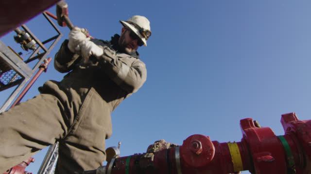 slow motion shot av en oljefält worker i trettioårsåldern pumpa ner linjer och slå ett rör med en hammare på en olja och gas drilling pad site på en kall, solig, winter morning - hammare bildbanksvideor och videomaterial från bakom kulisserna