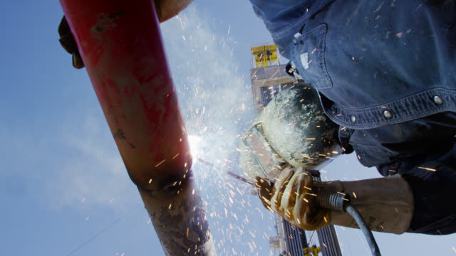 Slow Motion Shot of an Oilfield Worker Welding Two Pipes Together as Sparks Fly Next to a Derrick at an Oil and Gas Drilling Pad Site on a Sunny Day