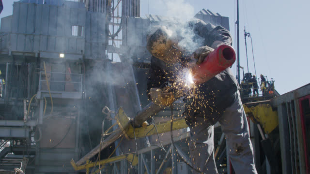 slow motion shot of an oilfield worker welding two pipes together as sparks fly next to a derrick at an oil and gas drilling pad site on a sunny day - работник физического труда стоковые видео и кадры b-roll