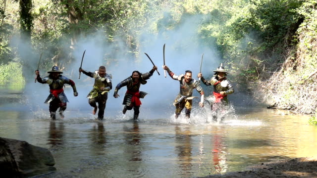 Slow Motion Shot Of Ancient Warriors Running And Shouting To Fight With Enemy At The River