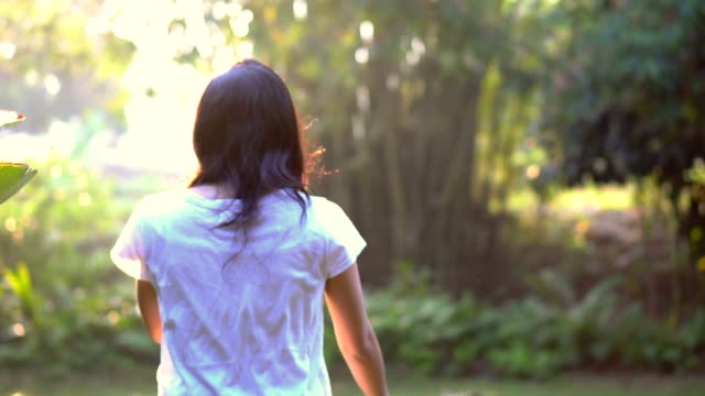 Slow motion shot of Asian woman walking in green morning nature video