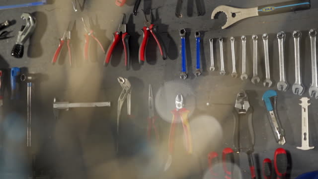 slow motion shot of bike tools through the inner workings of a mountain bike - pinze attrezzo manuale video stock e b–roll