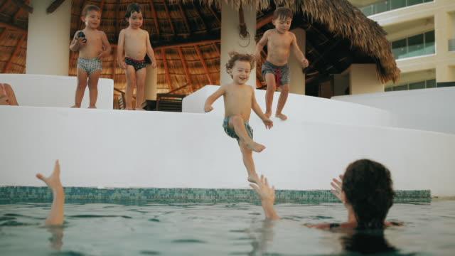 Langsamer Bewegungsschuss von Jungen, die ins Schwimmbad spielen – Video