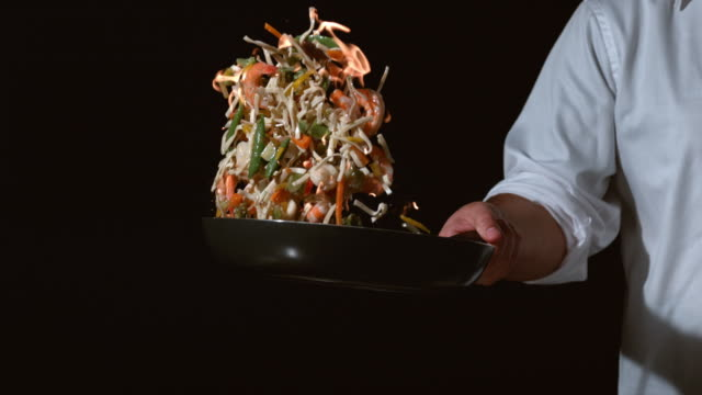 Slow motion shot of chef with flaming stir fry Slow motion shot of chef with flaming stir fry; shot on Phantom Flex 4K at 1000 fps stir fried stock videos & royalty-free footage